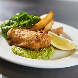 Spiced fish and chips with yoghurt pea puree